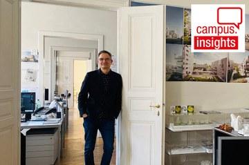 Architekt Sascha Bradic lehnt im Architektur-Büro in einem klassischen Altbau mit weißen Flügeltüren an einem Türrahmen und lächelt in die Kamera - im Raum sieht man Bilder und Modelle von Bauprojekten
